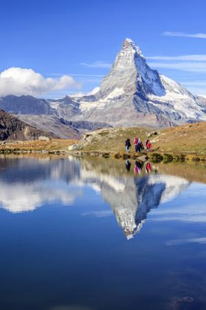 Hikers Walking on the Path Beside the Stellisee with the Matterhorn Reflected by Roberto Moiola