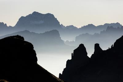 Mist on peaks of Dolomites and Monte Pelmo seen from Cima Belvedere at dawn, Val di Fassa, Trentino by Roberto Moiola