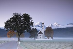Pink sunrise and mist of autumn on St. Coloman Church framed by snowy peaks, Schwangau, Bavaria, Ge by Roberto Moiola