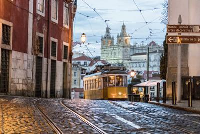 Romantic Atmosphere in Old Streets of Alfama with Castle in Background and Tram Number 28 by Roberto Moiola