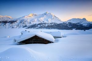 Some Scattered Huts in a Snowy Landscape at Spluga by the Maloja Pass with Magical Sunset Colors by Roberto Moiola