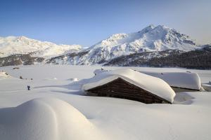 Some Spluga Huts Near the Maloja Pass Submerged by Meters of Powder Snow on a Clear Winter Day by Roberto Moiola