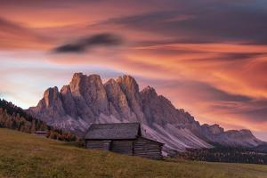 Sunrise over the Odle peaks and traditional hut in Gampen Alm, Italy by Roberto Moiola