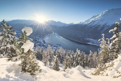 Sunrise over village and Lake of St. Moritz covered with snow, Engadine, Switzerland by Roberto Moiola