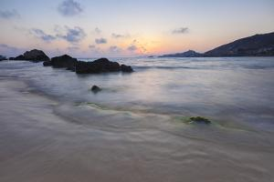 The last lights of the sunset are reflected on sea waves and sandy beach, Licata, Province of Agrig by Roberto Moiola