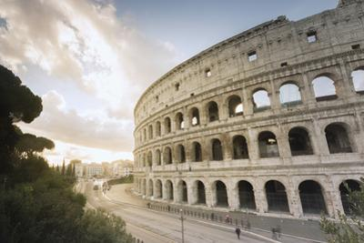 The lights of sunrise frame the ancient Colosseum (Flavian Amphitheatre), UNESCO World Heritage Sit by Roberto Moiola