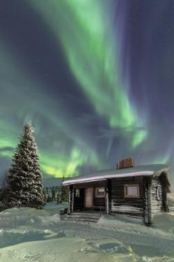 The Northern Lights (Aurora borealis) frame the wooden hut in the snowy woods, Pallas, Yllastunturi by Roberto Moiola