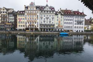 The typical buildings of the old medieval town are reflected in River Reuss, Lucerne, Switzerland,  by Roberto Moiola
