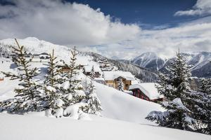 The Winter Sun Shines on the Snowy Mountain Huts and Woods, Bettmeralp, District of Raron by Roberto Moiola