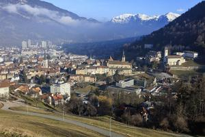 View of the city of Chur surrounded by woods and snowy peaks, district of Plessur, Canton of Graubu by Roberto Moiola