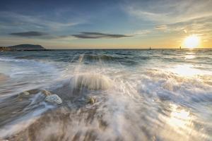 Waves crashing on the sandy beach framed by sunrise, Porto Recanati, Conero Riviera, Marche, Italy by Roberto Moiola