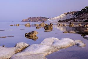 White cliffs known as Scala dei Turchi frame the calm sea at dawn, Porto Empedocle, Province of Agr by Roberto Moiola