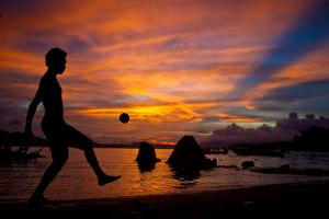 A Solomon Islander Kicks a Ball Against a Stunning Sunset Off Tetapare by Robin Moore