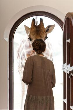 A Woman Greets a Rothschild Giraffe at the Door of a Lodge by Robin Moore