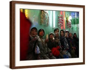 Afghan Boys Watch a Movie on a Television, Unseen, as They Eat Ice Cream at an Ice Cream Shop by Rodrigo Abd