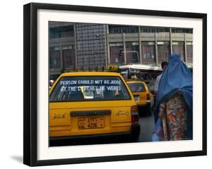 An Afghan Woman Clad in a Burqa Walks Next to a Taxi in Kabul, Afghanistan, Wednesday, June 7, 2006 by Rodrigo Abd