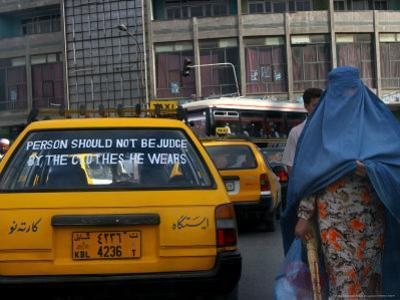 An Afghan Woman Clad in a Burqa Walks Next to a Taxi in Kabul, Afghanistan, Wednesday, June 7, 2006