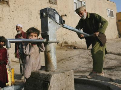 An Elderly Man Pumps Water from a Public Well in Kabul, Afghanistan, Friday, September 22, 2006
