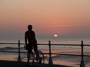 A Cyclist Pauses to Watch the Sunrise, on an Overlook Along the Ocean Front by Roff Smith