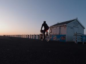 A Man Rides His Bicycle at Sunrise on the Sea Front in Bexhill by Roff Smith