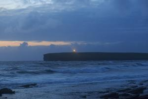 The Birsay Lighthouse Flickers to Life on a Wet and Windy Dusk Off the North Coast of Mainland Isla by Roff Smith