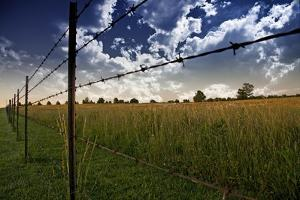 Clouds in Sky and Farmers Fence and Field by rolffimages
