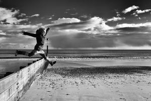 Female Figure Jumping on a Beach by Rory Garforth