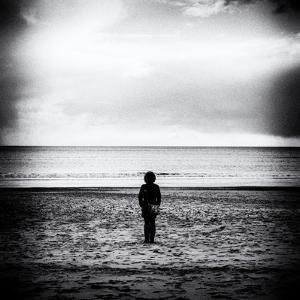 Female Figure Standing Alone on Beach by Rory Garforth