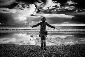 Young Girl Standing on a Beach by Rory Garforth