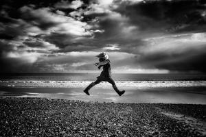 Young Woman Jumping on Beach by Rory Garforth