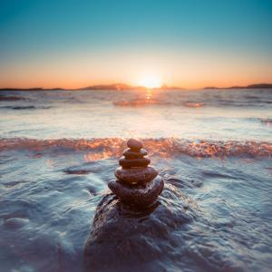 Round Smooth Stones in Pyramid Form by Sea with Wave Coming in during Golden Sunset
