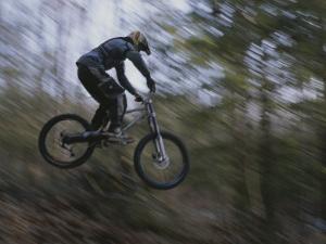 A Boy Flies Through the Air on His Mountain Bike by Roy Gumpel