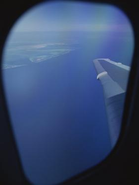 A View out of an Airplane Window over Water and Nearby Islands by Roy Gumpel