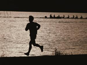 Silhouette of a Jogger Next to Water by Roy Gumpel