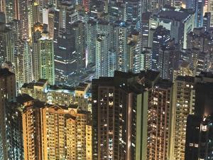 Apartment buildings in Hong Kong at night by Rudy Sulgan