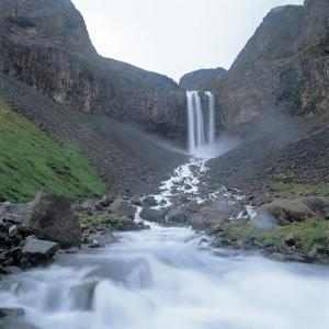 Rushing and Cascading Waterfall Between Mountains