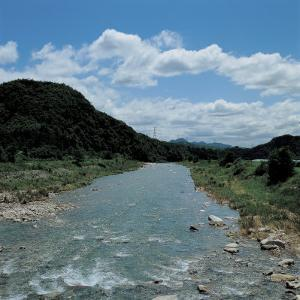 Rushing River Through Valley with Rocks and Mountains