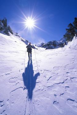 Backcountry skier crossing wind blown snow near Treasure Lakes, John Muir Wilderness, California by Russ Bishop