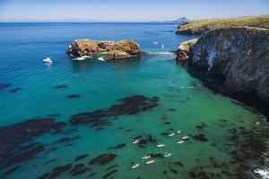 Kayaks and sailboats at Scorpion Cove, Santa Cruz Island, Channel Islands NP, California, USA. by Russ Bishop