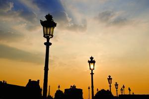 Street lamps at sunset, Louvre Museum, Paris, France by Russ Bishop