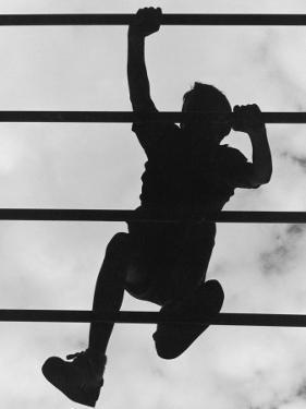 Boy Climbing on Jungle Gym by Russell Burden