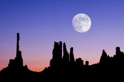 Dawn Silhouette of the Totem and Yei Bi Chi Formations with Large Full Moon in Monument Valley, Ari