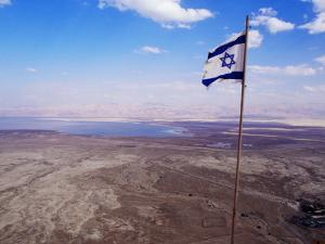 The Blue and White Flag of Israel, the Star of David Flies over the Deserts of Masad by Russell Mountford