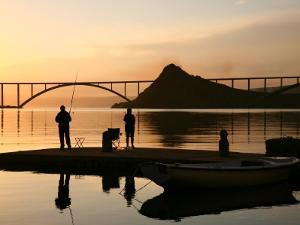 Couple Fishing from Stone Pier with Krk Bridge Joining Krk Island to Mainland by Ruth Eastham & Max Paoli