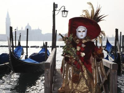 Masked Person in Costume by Gondolas Near St. Mark's Square