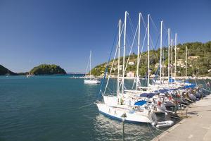 View across Lakka Bay, Yachts Lined Up Along the Quay, Lakka by Ruth Tomlinson