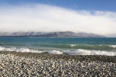 View from rocky shoreline across the stormy waters of Lake Pukaki, near Twizel, Mackenzie district,