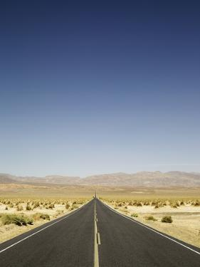 Long Road in Desert with Blue Sky. by Ryan Mcvay