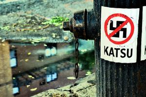 Katsu Sticker and Crossed-Out Swastika on a Lamppost, Manhattan by Sabine Jacobs