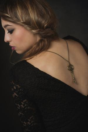 Young Woman Wearing Black Dress with Key on Necklace